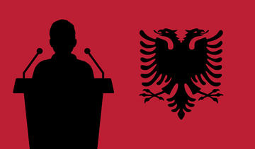 A stylized figure speaking behind a lectern, on his right the double-headed eagle of the Albanian flag