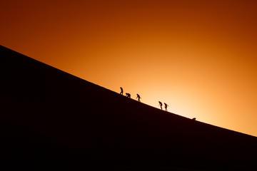 Figure in controluce cercano di scalare una collina © danm12/Shutterstock
