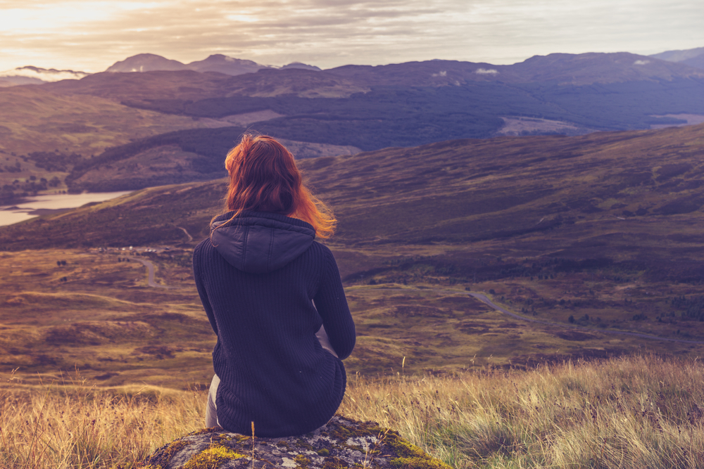 Donna seduta su una montagna in contemplazione © Lolostock/Shutterstock
