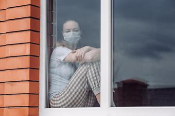 Woman at the window during lockdown (© Tatyana Blinova/Shutterstock)