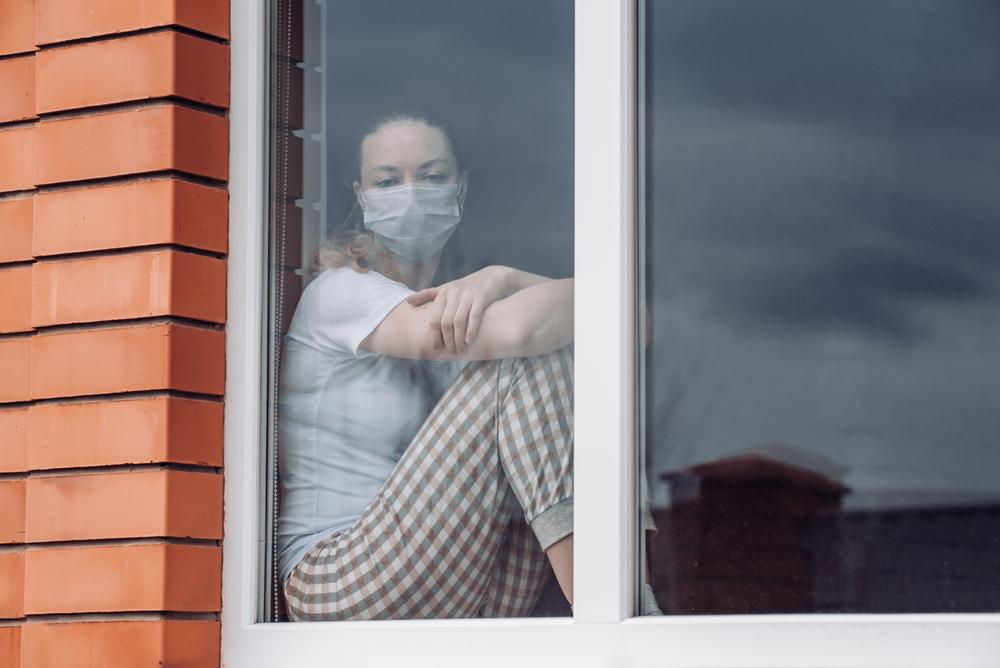 زن در حالی که قفل در پنجره است (© تاتیانا بلینوا / شاتر استوک)