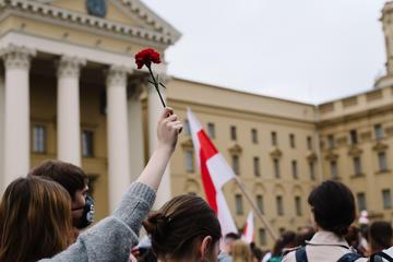 Una donna alza la mano reggendo una rosa rossa nel bel mezzo di una proptesta pacifica nella caitale della Bielorussia, 23 agosto 2020 (© Alex_Bar/Shutterstock)