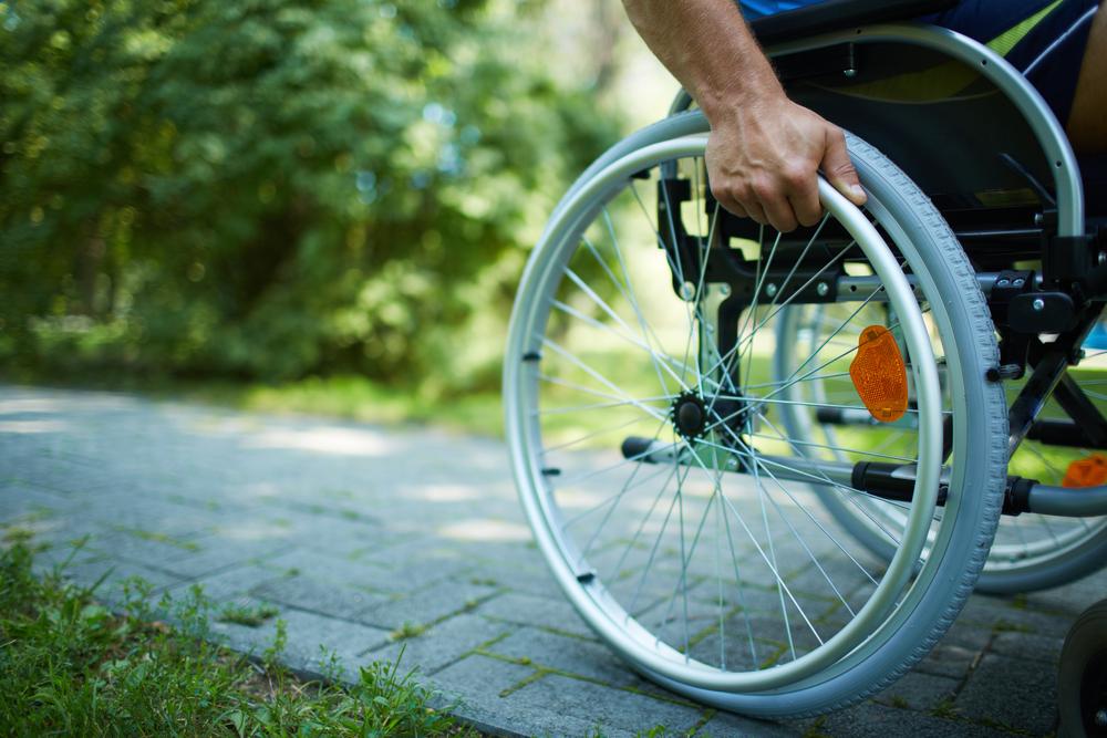 Primo piano di una mano maschile su ruota della sedia a rotelle durante la passeggiata nel parco - © Pressmaster/Shutterstock