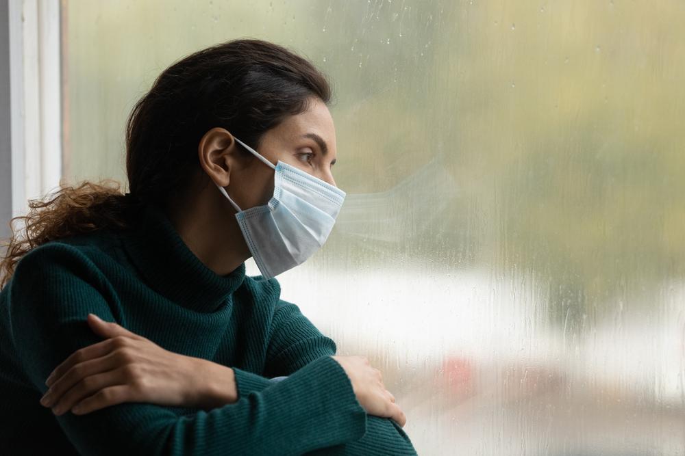 Donna con mascheria riflette triste davanti ad un vetro