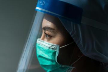 Viso di una dottoressa con indosso mascherina e lastra di plexiglas © theskaman306/Shutterstock