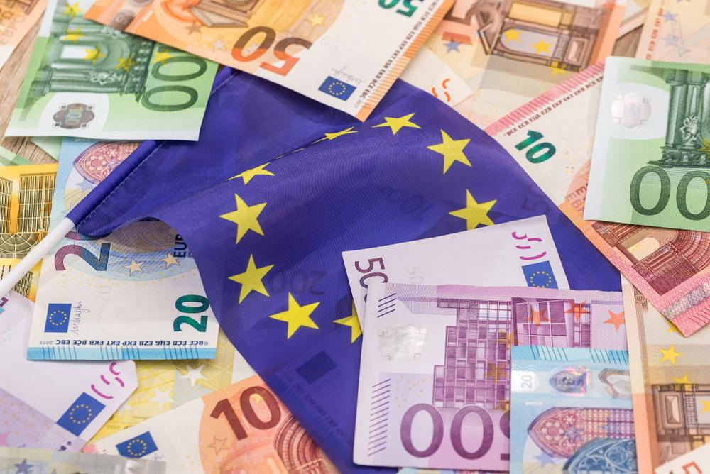 Banconote di euro di diverso taglio sparse su un piano con al centro la bandiera dell'UE (© RomanR/Shutterstock)