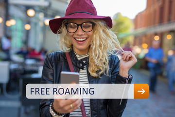 Una ragazza sorride guardando al proprio cellulare © Kaspars Grinvalds/Shutterstock