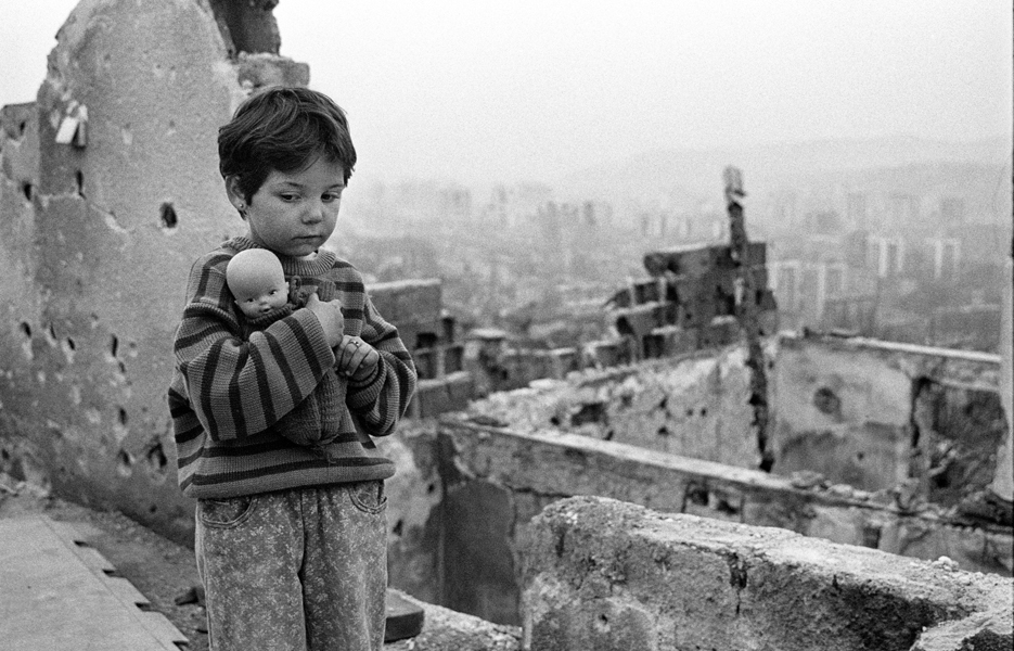 Sarajevo 1996, una bambina con lo sguardo triste tiene in braccio una bambola senza capelli, sullo sfondo la città in macerie - foto © Mario Boccia