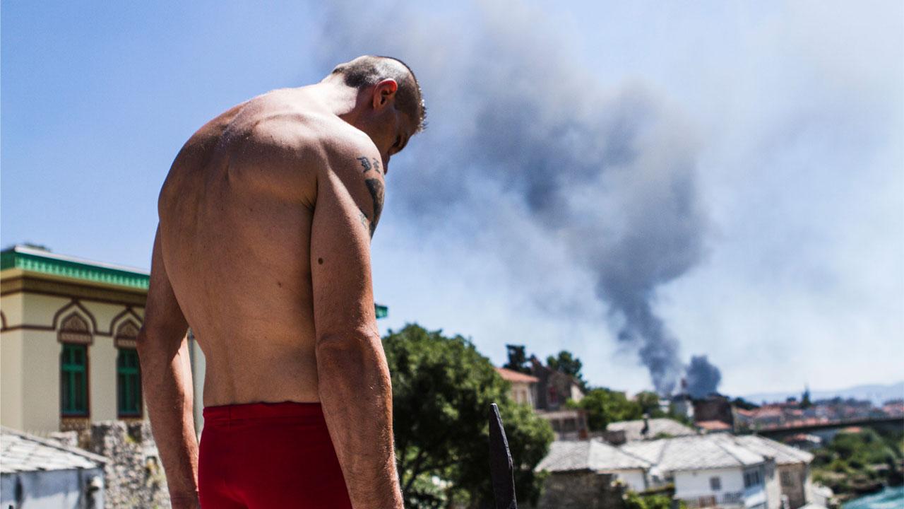 """Un uomo guarda giù dal ponte pronte a tuffarsi nel fiume Neretva a Mostar (screenshot tratto dal film """"I tuffatori"""" di Daniele Babbo)"""