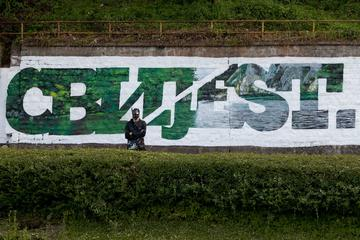 "Graffiti created by Manu Invisibile in Srebrenica - ""Awareness"", written in part in Cyrilic and in part in Latin alphabet"