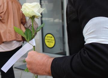 Una persona che regge una rosa bianca ed ha una fascia bianca al braccio