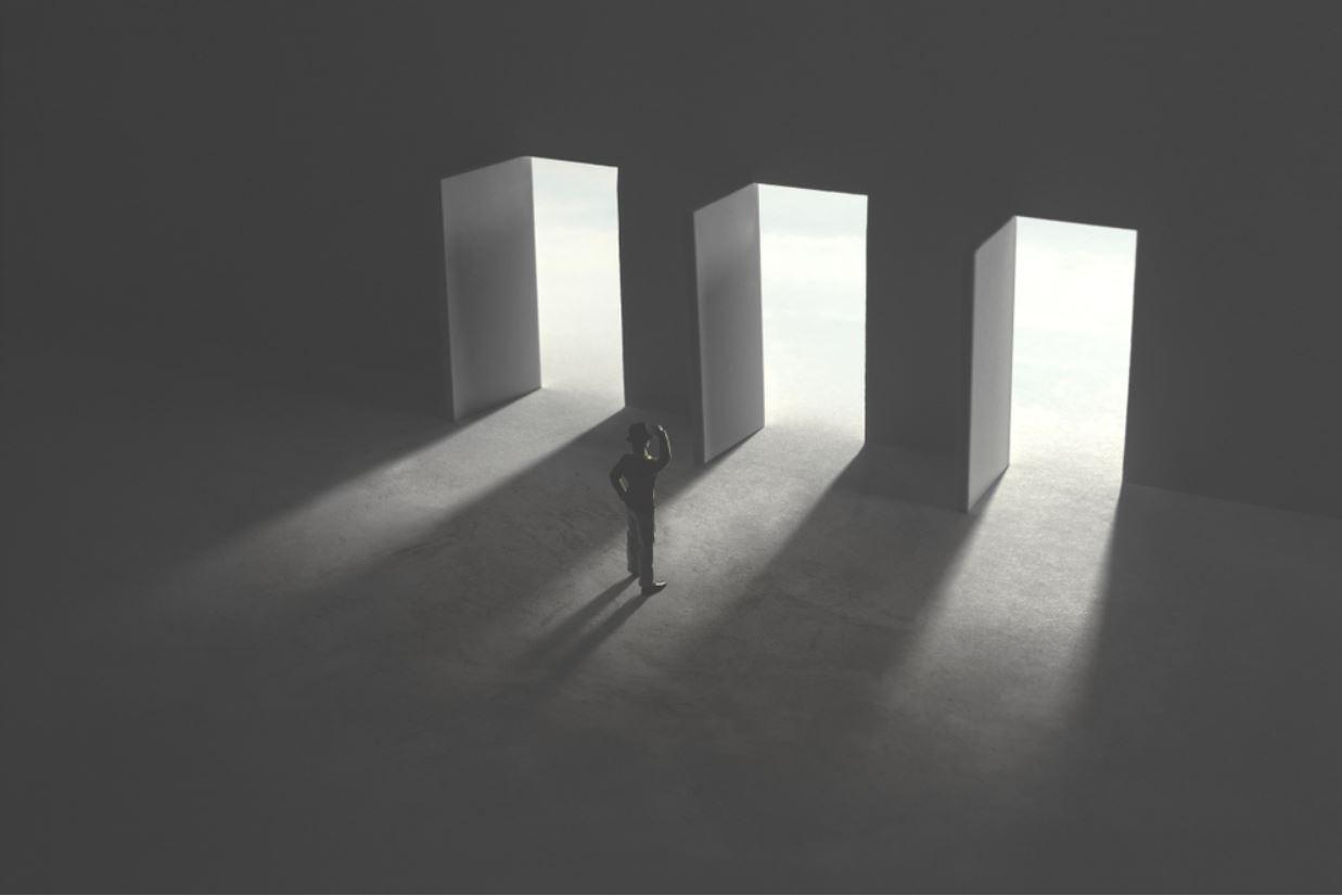 Rappresentazione di un uomo in dubbio di fronte a tre porte aperte - © fran_kie/Shutterstock