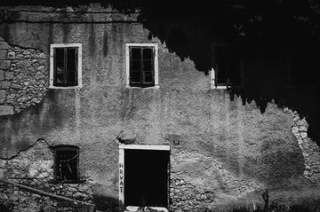 """Una facciata fessurata di una casa, con la scritta """"croato"""" su una delle finestre © Igor Čoko"""