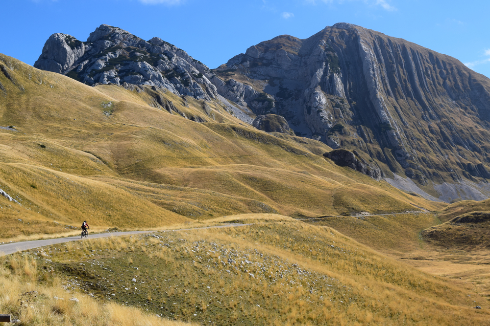 A cyclist along a road in the mountains in Montenegro - © NOYMES/Shutterstock