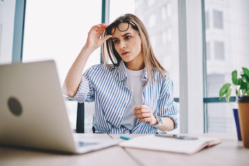 Donna legge con disappunto qualcosa sul suo portatile © GaudiLab/Shutterstock