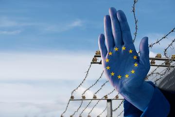Mano dipinta con i colori della bandiera europea davanti ad una rete di filo spinato (© Maren Winter/Shutterstock)