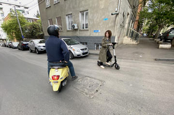 A motorised and electric scooter rider stop to chat at a crossroads during the COVID-19 state of emergency when most motorised transportation was prohibited in Tbilisi