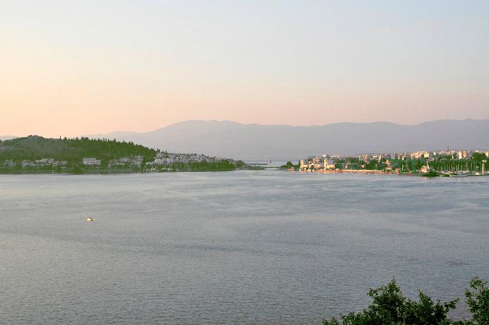 Lo stretto dell'Euripo con il famoso ponte. Sulla destra, il centro di Calcide, alle cui spalle si levano i grandi monti dell'isola Eubea. A sinistra, la Grecia continentale