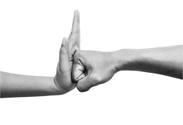 Una mano femminile ferma un pugno maschile - rappresentazione della lotta alla violenza di genere