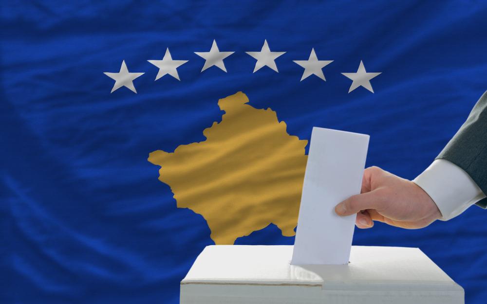 صندوق رأی با درج دستی رأی در صندوق رأی ، پس زمینه پرچم کوزوو (عکس © vepar5 / Shutterstock)