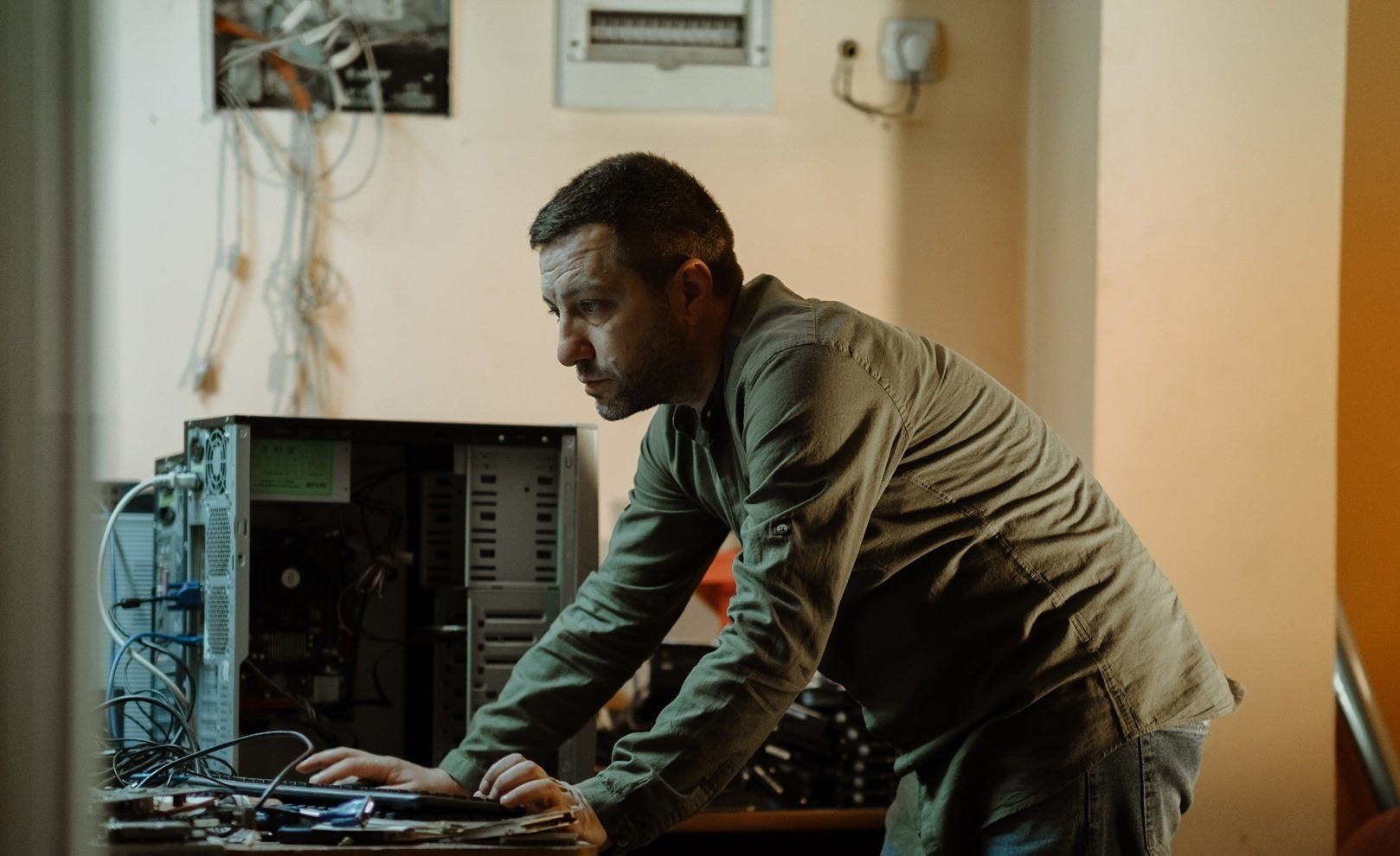 """Borce Stamenov at work repairing a computer - photo taken from the Facebook profile of the """"Donate a computer"""" initiative"""