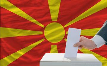 Elettore che inserisce la scheda sullo sfondo della bandiera della Macedonia del nord -  © vepar5/Shutterstock