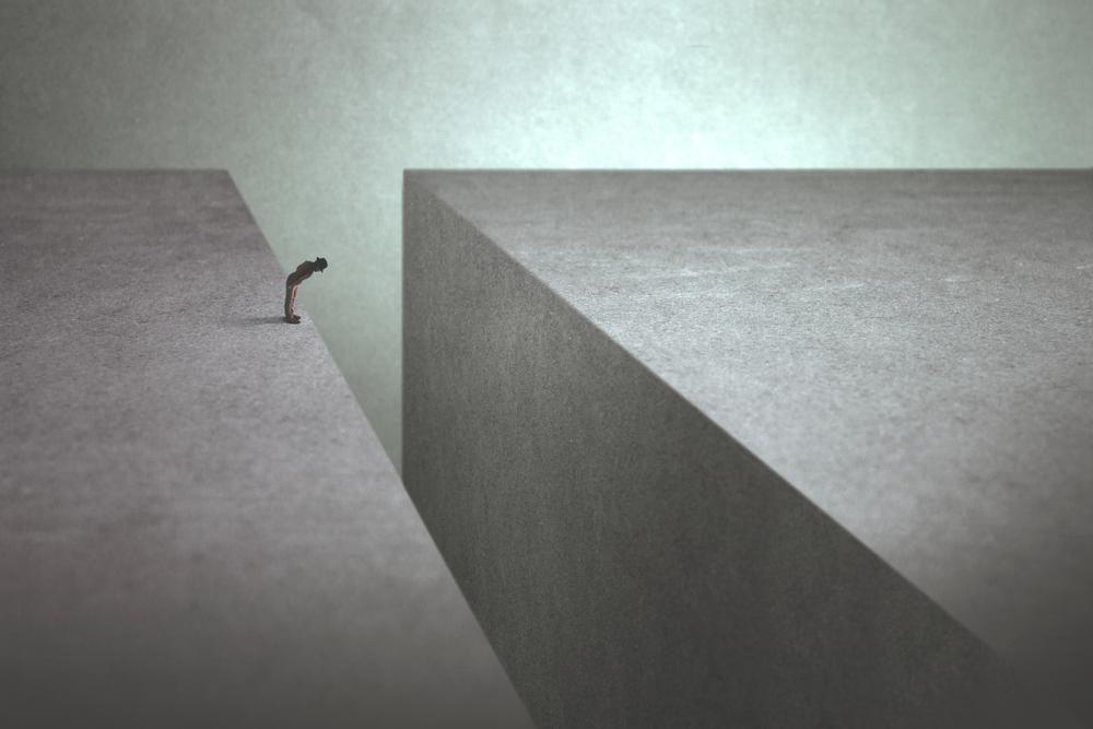 Un uomo sul bordo di una spaccatura guarda in basso temendo di saltare (© fran_kies/Shutterstock)