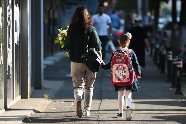A mother, photographed from behind, accompanies her daughter to school