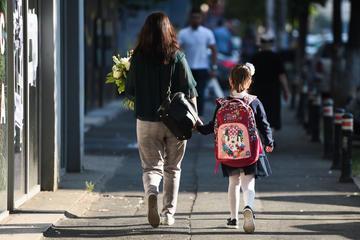 Una madre, fotografata di spalle, accompagna propria figlia a scuola
