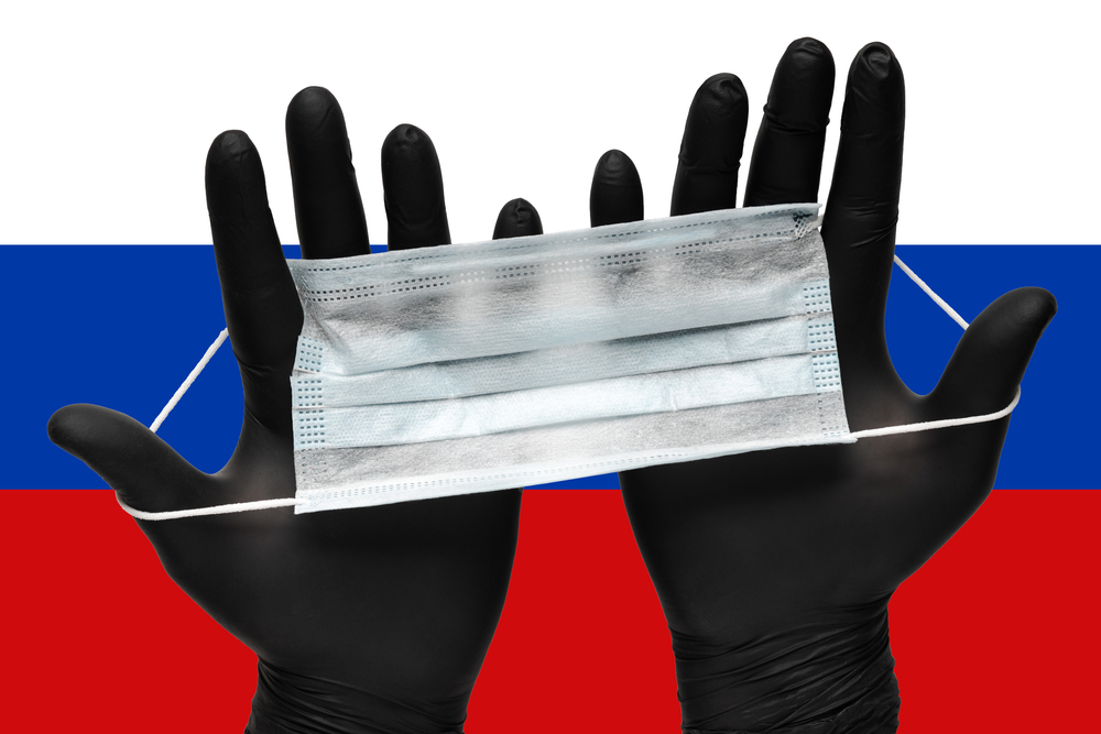 Two hands in black gloves hold a face mask with the Russian flag in the background