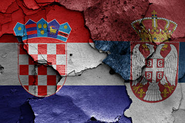 Bandiera croata e bandiera serba dipinte  una accanto all'altra su un muro fessurato  (©danielo/Shutterstock)