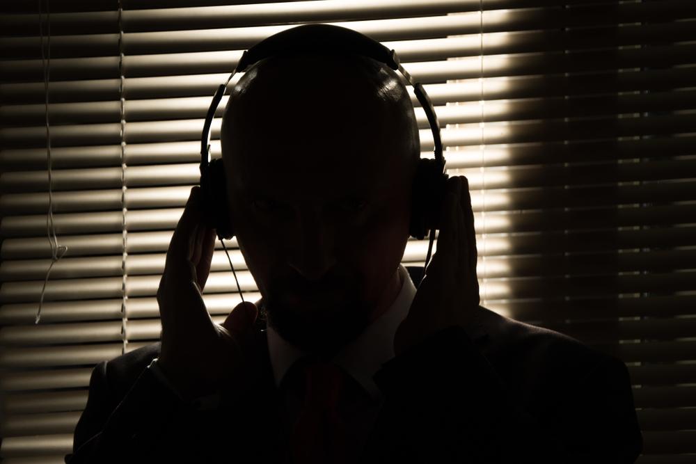 Uomo nell'ombra che ascolta con delle cuffie (© Anelo/Shutterstock)