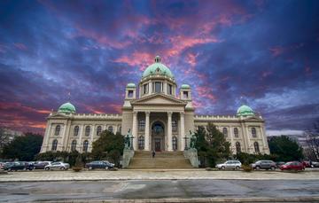 L'immagine ritrae il parlamento serbo sotto un cielo tempestoso