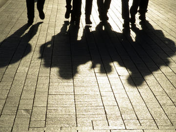Shadows of men walking on the sidewalk (© Oleg Elkov/Shutterstock)