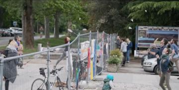 Ragazzi giocano a badminton lungo la rete installata per dividere la Piazza della Transalpina a Gorizia/Nova Gorica
