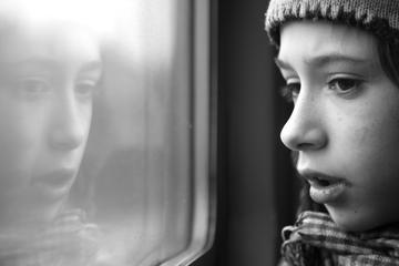 Bambino guarda fuori dal finestrino di un treno