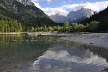 Bimbo salta da un sasso all'altro nel lago Jasna a Kranjska Gora
