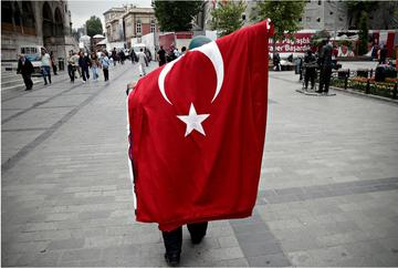 A man carries the Turkish flag on his shoulders after a demonstration - © Alexandros Michailidis/Shutterstock