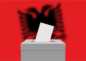 Urna elettorale con la bandiera albanese sullo sfondo - © grebeshkovmaxim/Shutterstock