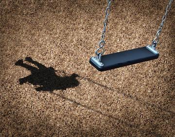 Un'altalena vuota e sul terreno l'ombra di una bambina