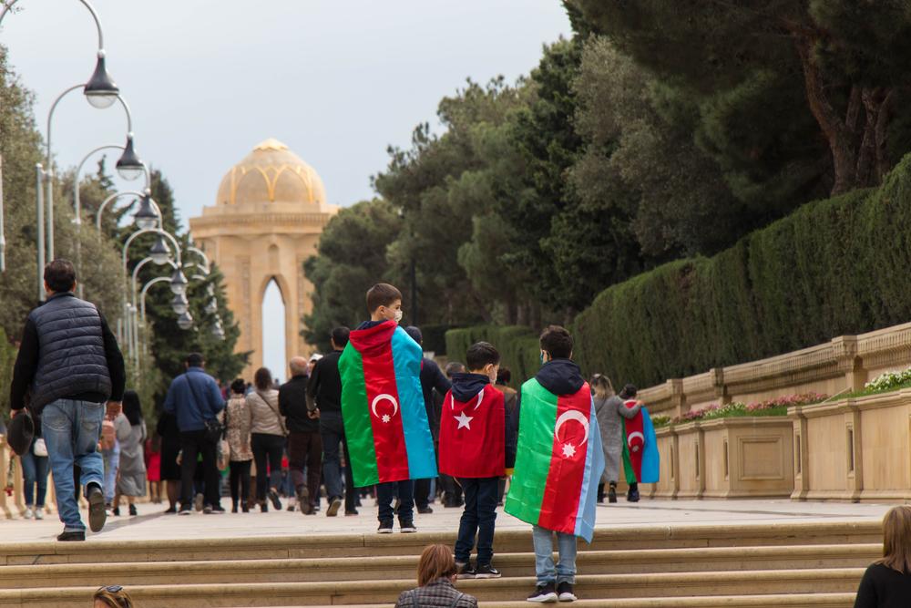 10 novembre 2020, a Baku, capitale dell'Azerbaijan, persone avvolte nella bandiera dell'Azerbaijan festeggiano la vittoria nella recente guerra contro l'Armenia (© Nurlan Mammadzada/Shutterstock)