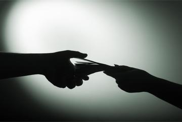 Mani che si passano denaro sporco - © spixel/Shutterstock