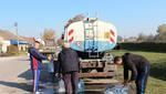 Gli abitanti di Glogonj riempiono le bottiglie dalla cisterna (foto CINS)