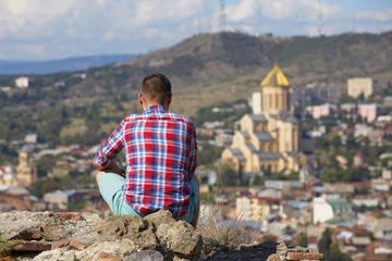 Un uomo pensieroso guarda Tbilisi da un'altura © Jaromir Chalabala/Shutterstock