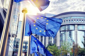 Bandiere dell'UE che sventolano davanti all'edificio del Parlamento europeo © symbiot/Shutterstock