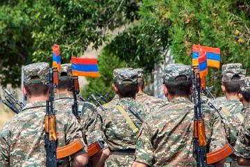 Soldati armeni fotografati di spalle con la bandiera armena infilata nella baionetta dei loro fucili - @ Artem Avetisyan/Shutterstock