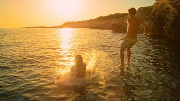 Due giovani saltano nell'acqua del mare in Croazia (© Flystock/Shutterstock)