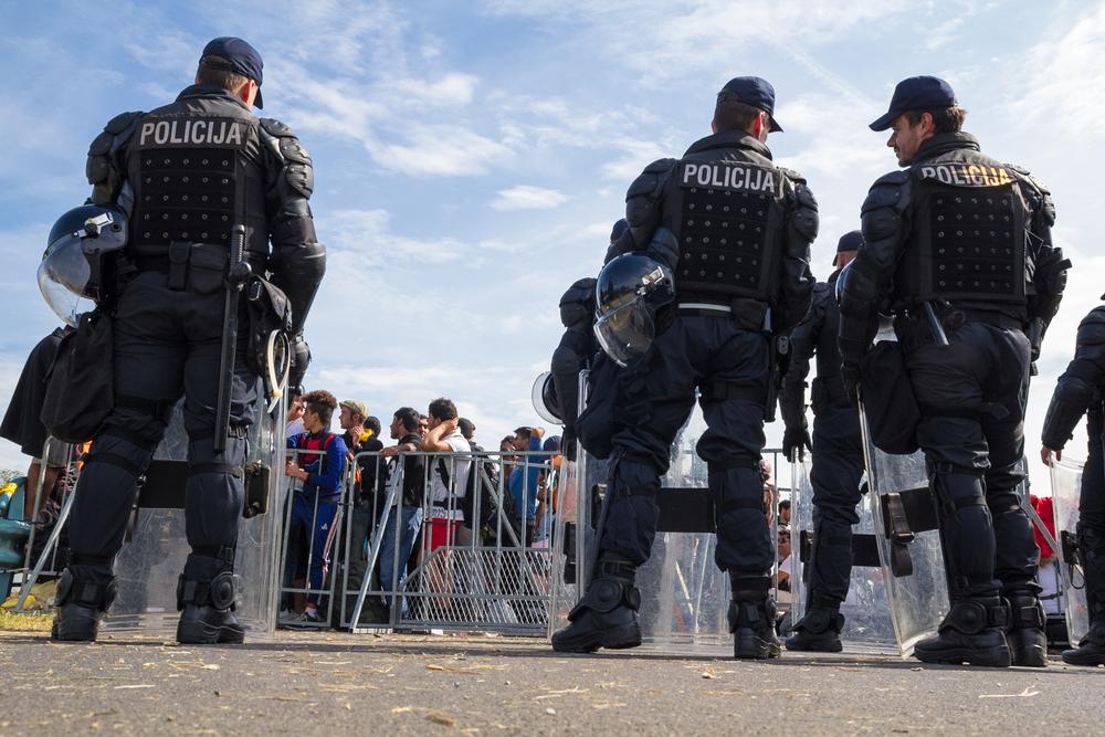 Alcuni poliziotti croati in tenuta anti sommossa stazionano davanti ad un transenna che li divide dalla massa di migranti al confine tra Croazia e Bosnia