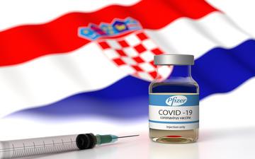 Fiale di vaccino anti covid19, sullo sfndo la bandiera croata (© Orpheus FX/Shiìutterstock)