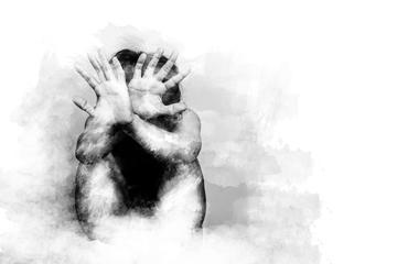 Un uomo si protege il volto e il corpo con le mani protese © asiandelight/Shutterstock
